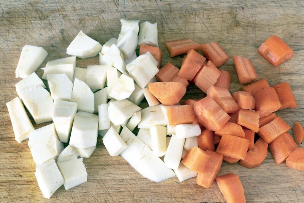 chopped parsnip and carrots on chopping board
