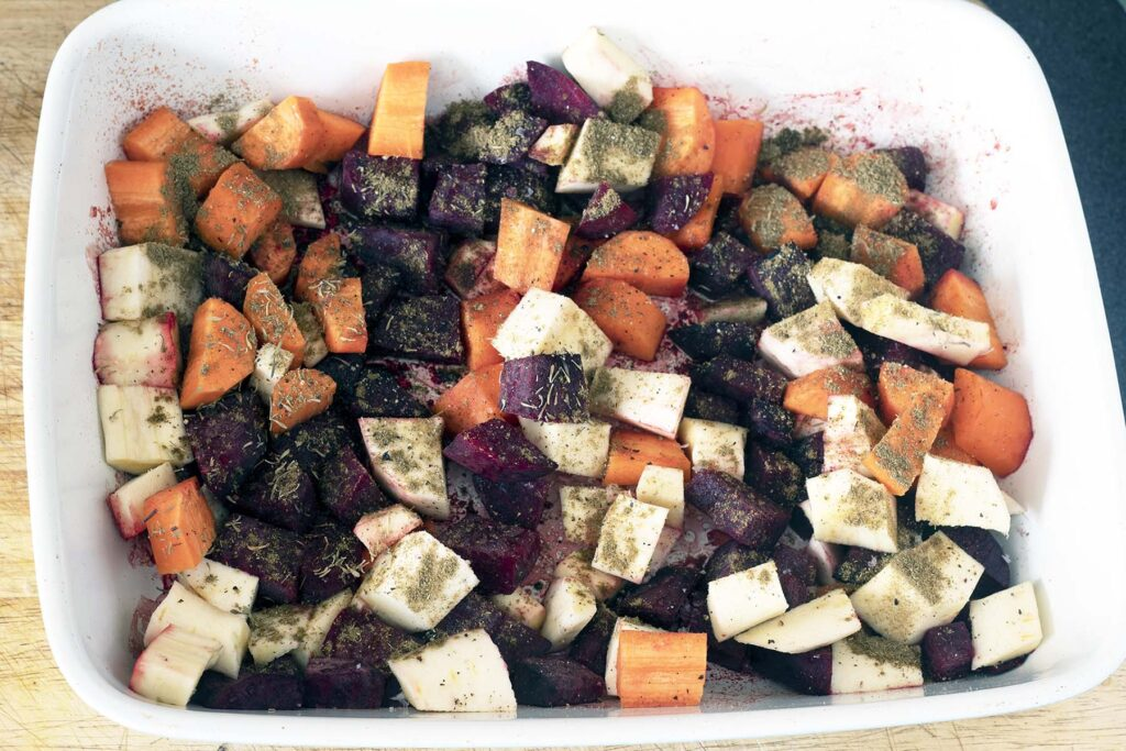partially cooked roasted rainbow root vegetables in ceramic baking dish with blue background