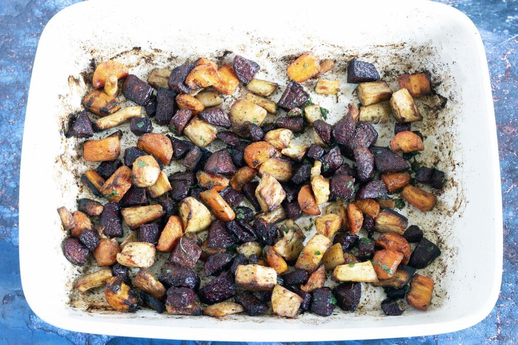 roasted rainbow root vegetables in ceramic baking dish with blue background
