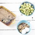overhead shot of gooseberry crumble in yellow dish with bowl of gooseberries and blue bowl with crumble and ice cream