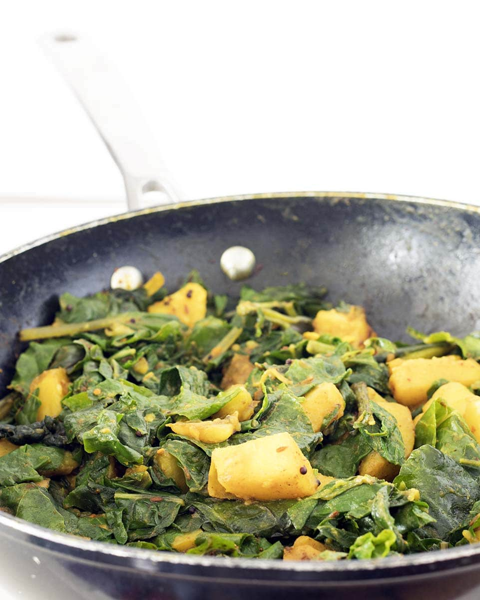 potato and spinach curry in wok