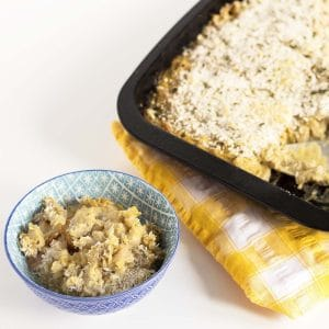 vegan butternut squash macaroni cheese in baking dish with a small portion in blue and white bowl