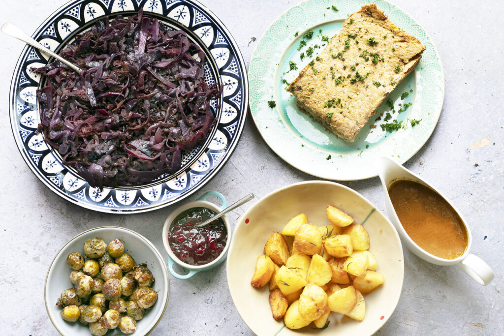 a vegan christmas dinner with cabbage, nut roast, potatoes, sprouts, sauce and gravy