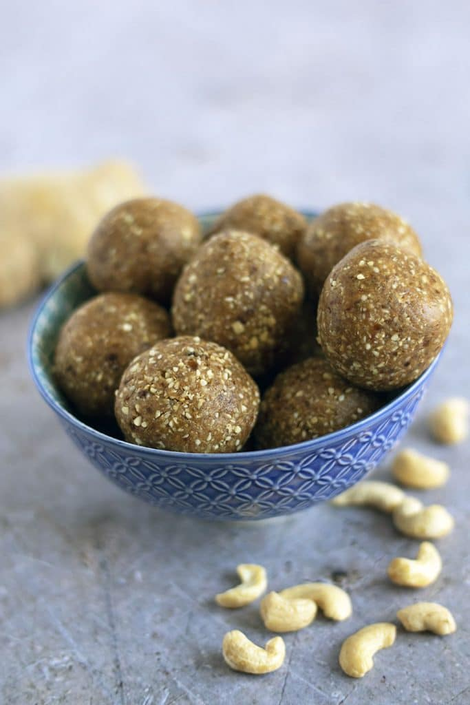 vegan energy balls in blue bowl with ginger and cashews on the table