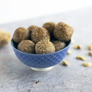 ginger energy balls in bowl with ginger and cashews