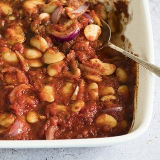 Greek-style baked beans with tomato sauce and dill in roasting tin