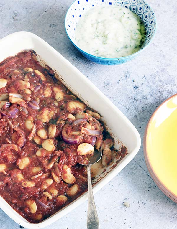 greek beans in dish with tzatziki and yellow plate