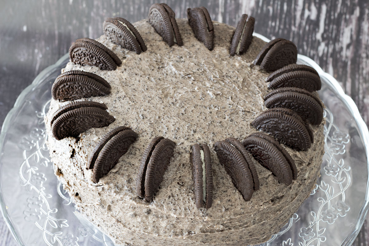 chocolate oreo cake by Cook Veggielicious. Cake on glass cake stand with wood background.