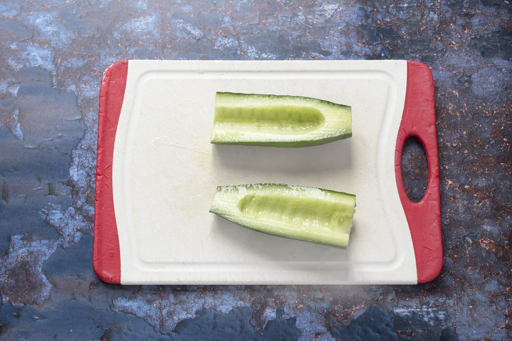halved cucumber on chopping board with seeds removed