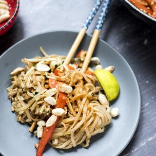 Vegan pad thai on grey plate with chopsticks. Recipe by Cook Veggielicious
