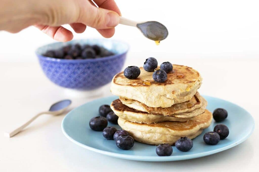 pancakes with blueberries and hand drizzling syrup
