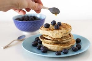 Vegan peanut butter pancakes with blueberries and maple drizzle