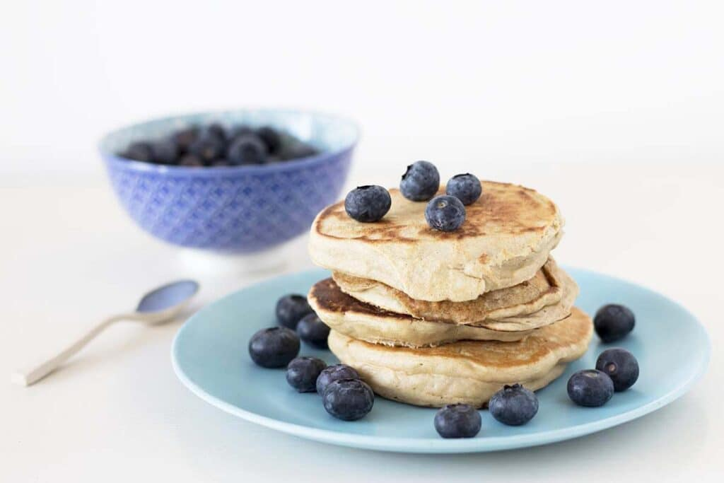 pancakes and blueberries on blue plate