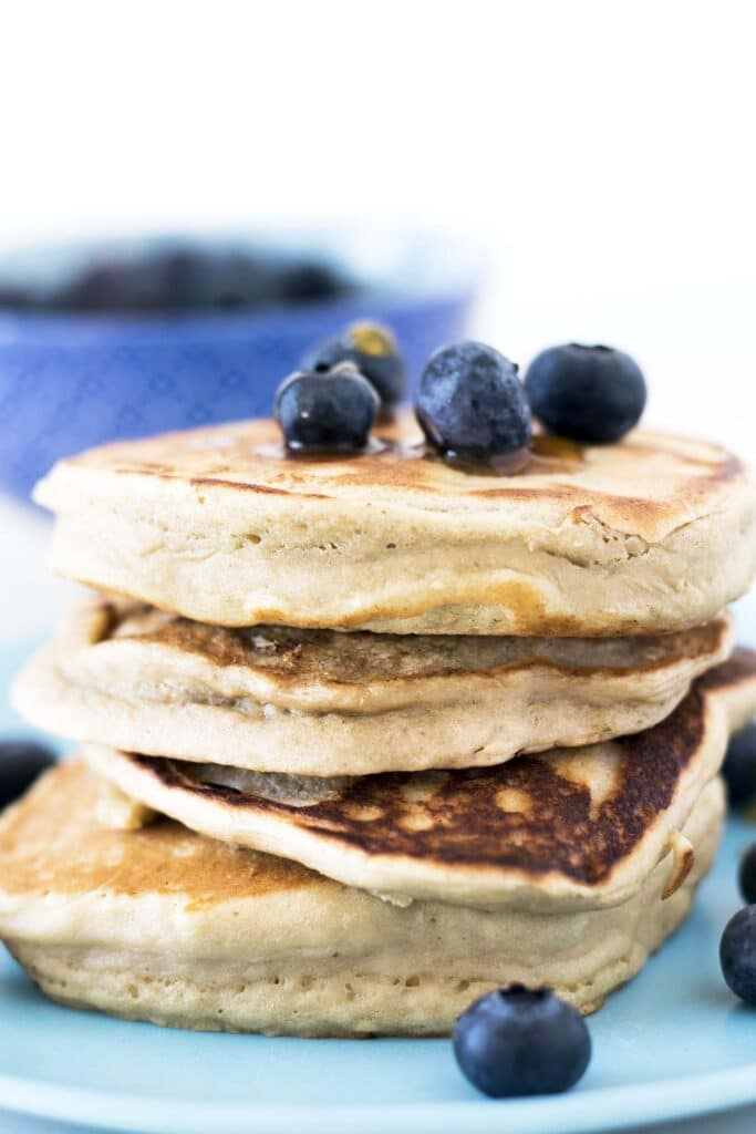vegan peanut butter pancakes on blue plate with blueberries