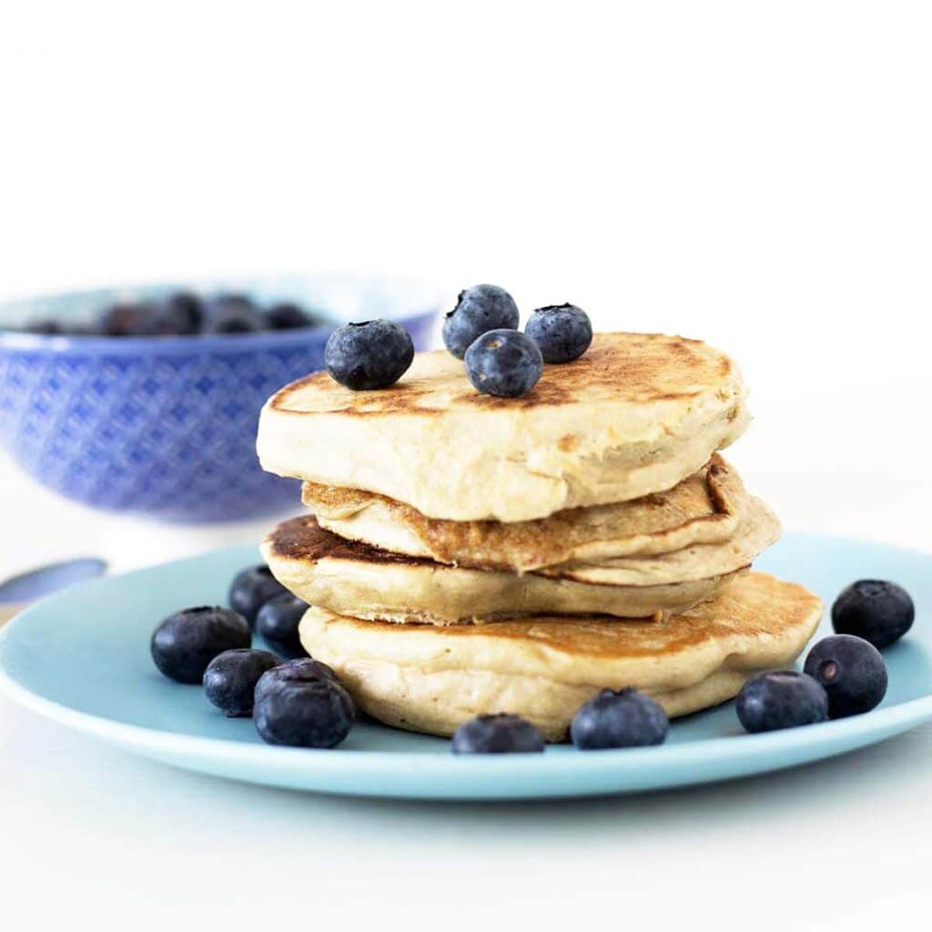 stack of peanut butter pancakes with blueberries on blue plate