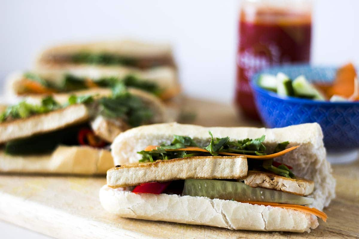 vegan tofu banh mi - baguette with tofu and salad on wooden board