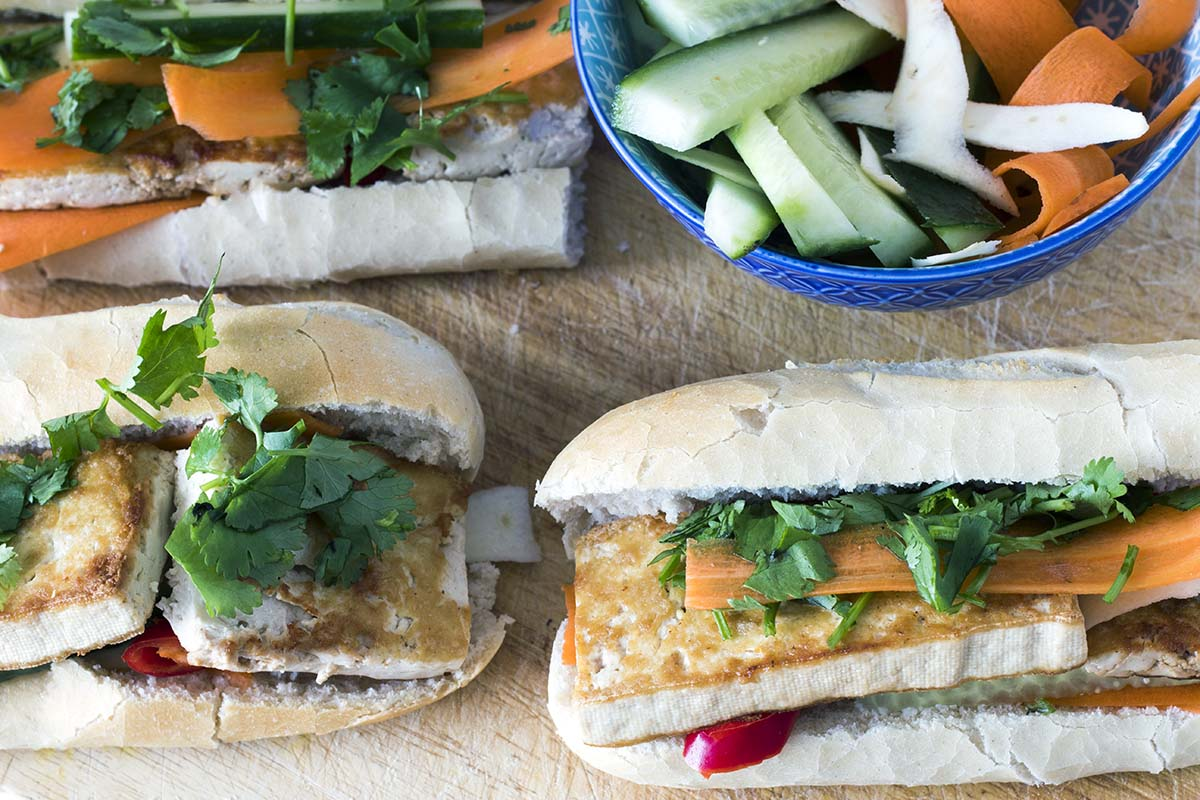Vegan banh mi with tofu and salad on wooden board