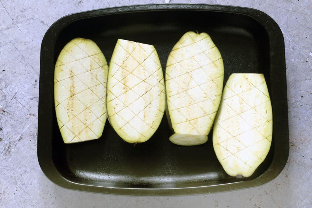 raw aubergines in roasting tin