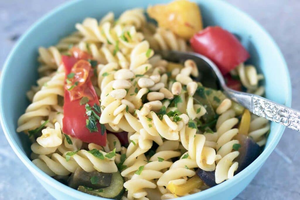 pasta twists and roasted vegetables in blue bowl