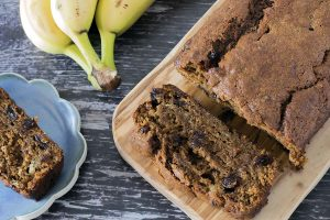 vegan banana bread on board with bananas in background