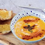 carrot soup topped with seeds in blue bowl