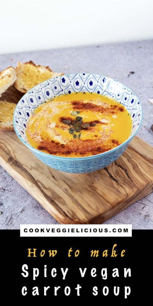 spicy carrot soup in blue bowl. Bread in background