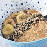 close up of banana porridge in blue bowl