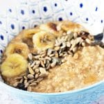 vegan porridge in bowl with bananas and seeds on top