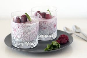 raspberry coconut chia pudding in glasses on grey plate with mint leaves in foreground
