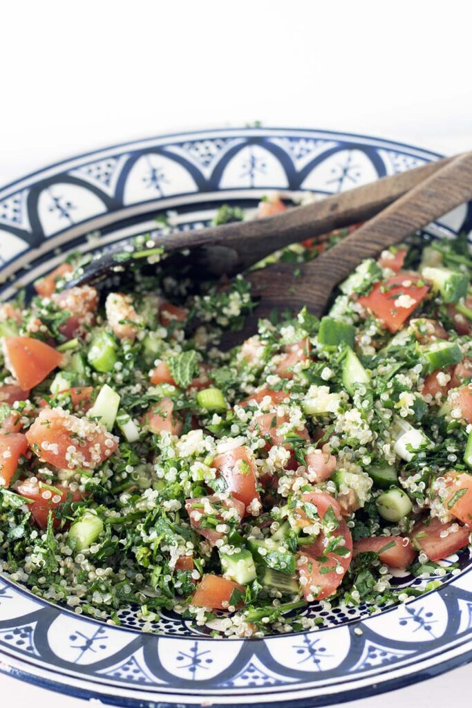 quinoa tabbouleh in moroccan bowl with wooden spoons