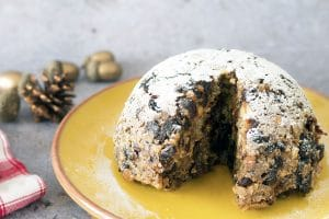 vegan christmas pudding on plate with decorations in background