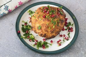 whole roasted cauliflower on plate with pomegranate seeds and herbs