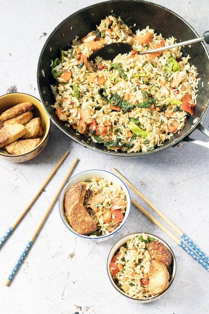 Overhead shot of Thai basil fried rice in wok and bowls with tempeh