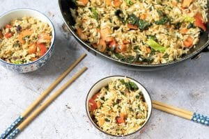 Thai basil fried rice in wok and rice bowls with chopsticks