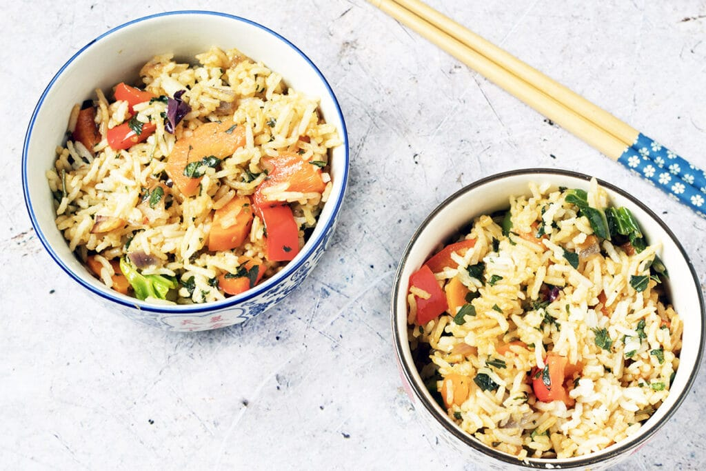 thai basil fried rice in wok and bowls