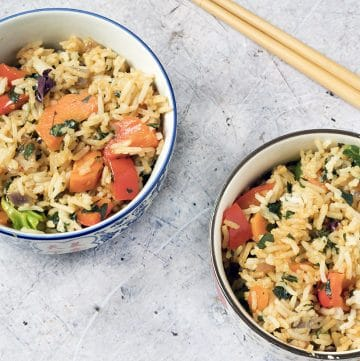 Thai basil fried rice in small rice bowls and chopsticks in background