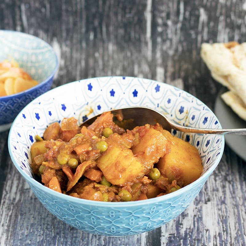 Indian root vegetable curry in blue and white bowl