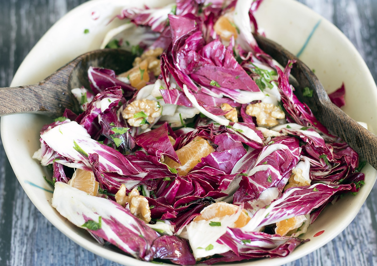 radicchio salad in bowl with clementines and walnuts