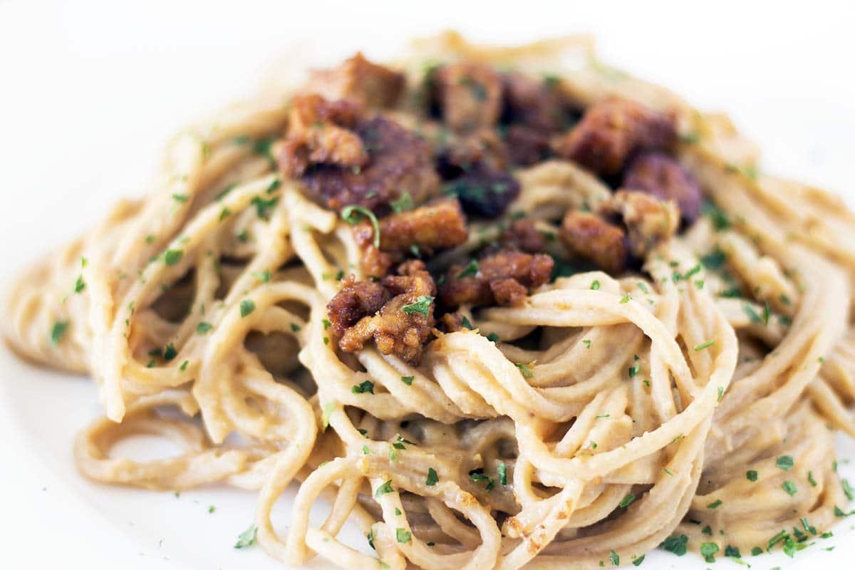smoky tempeh pieces with vegan spaghetti carbonara on white plate