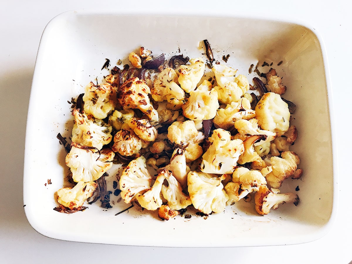 roasted cauliflower and red onion in roasting dish