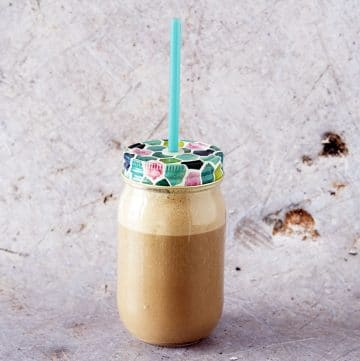 coffee smoothie in glass smoothie jar with straw on grey background