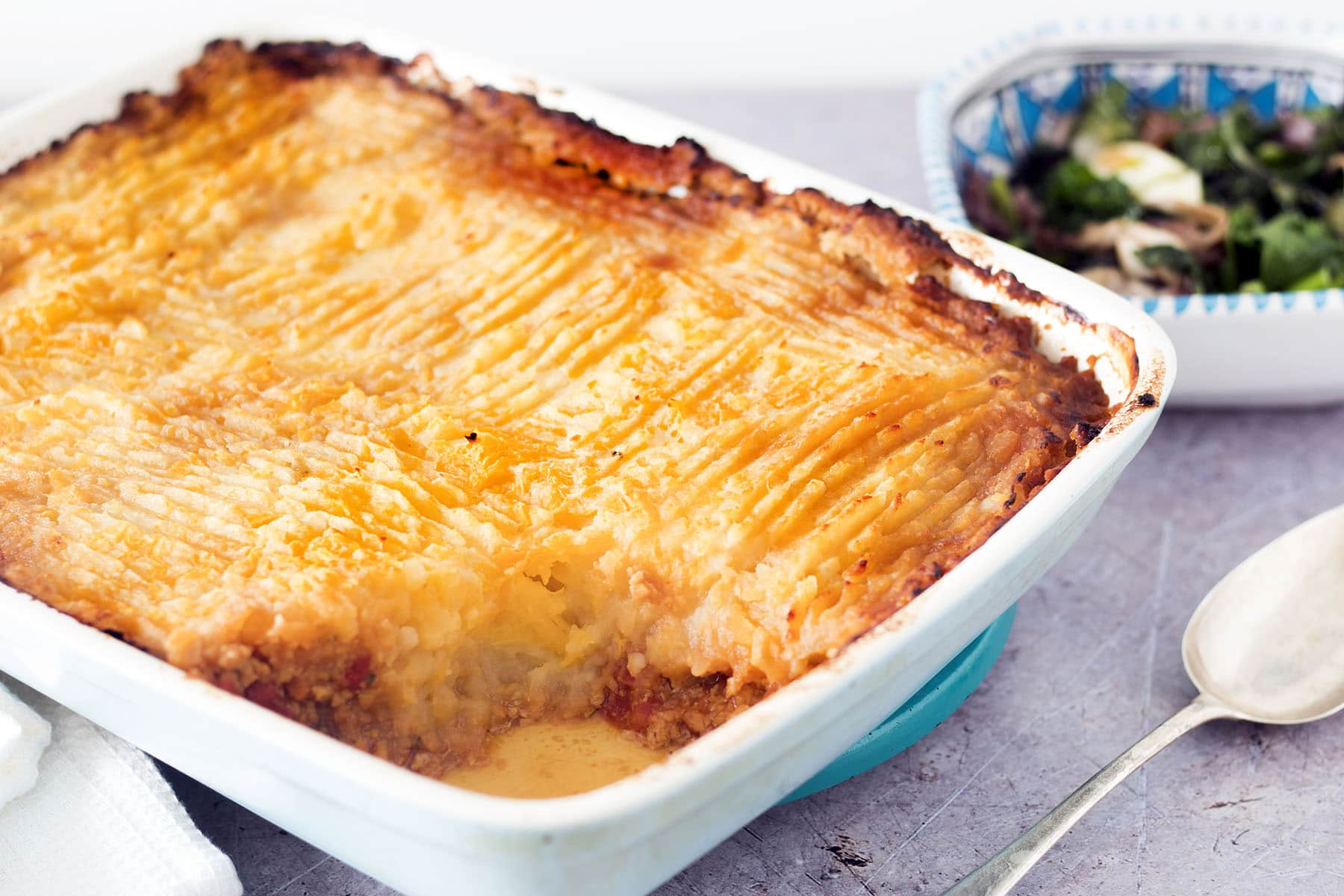 vegan shepherds pie in blue and white oven dish with greens in background