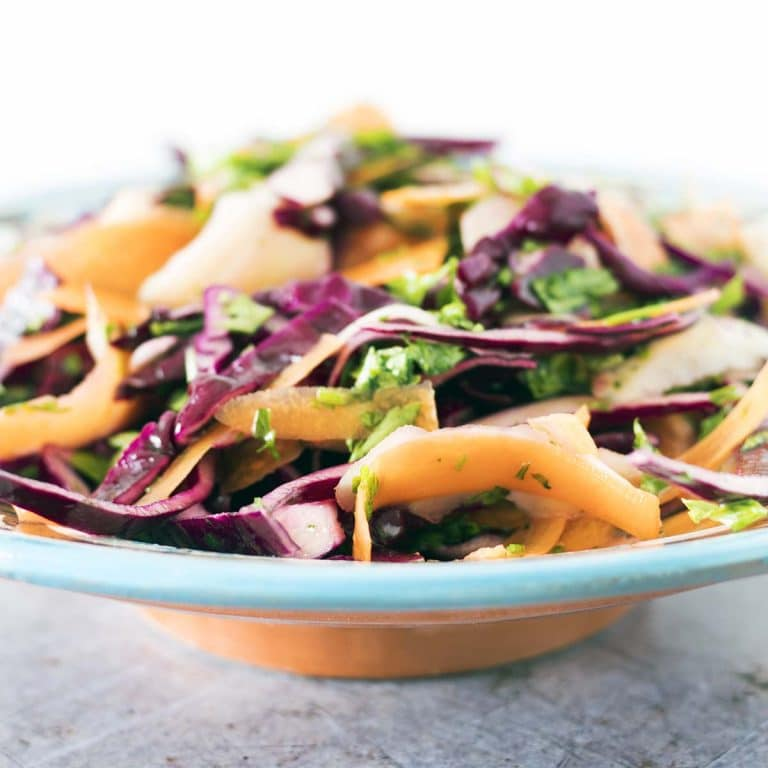 close up shot of kohlrabi, carrot and cabbage slaw in blue and white moroccan bowl
