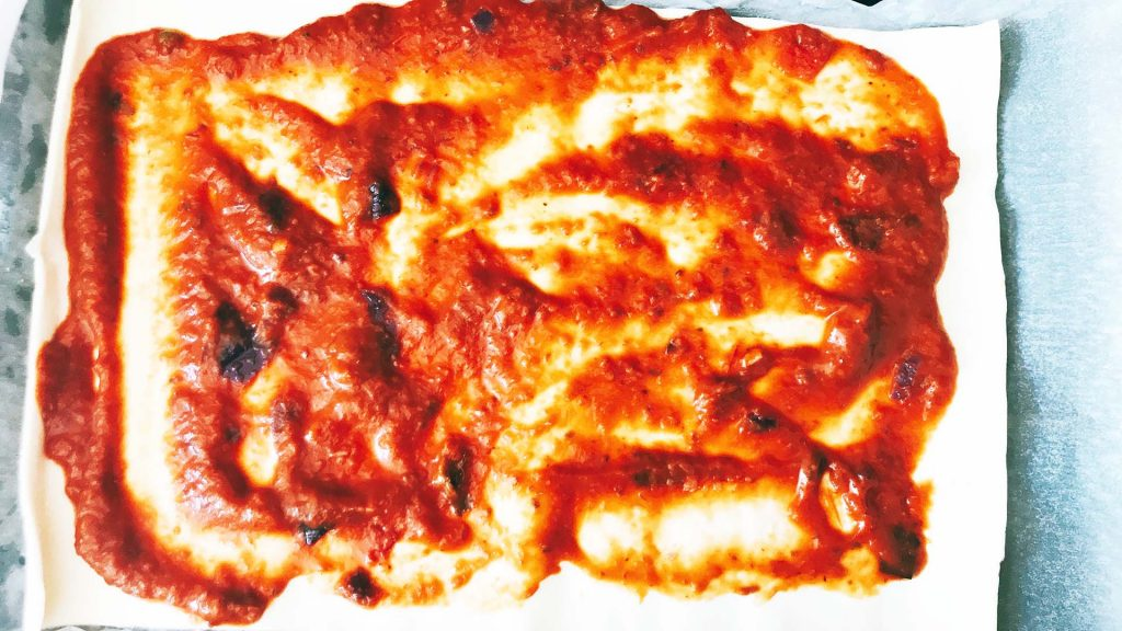 sheet of puff pastry covered with tomato sauce