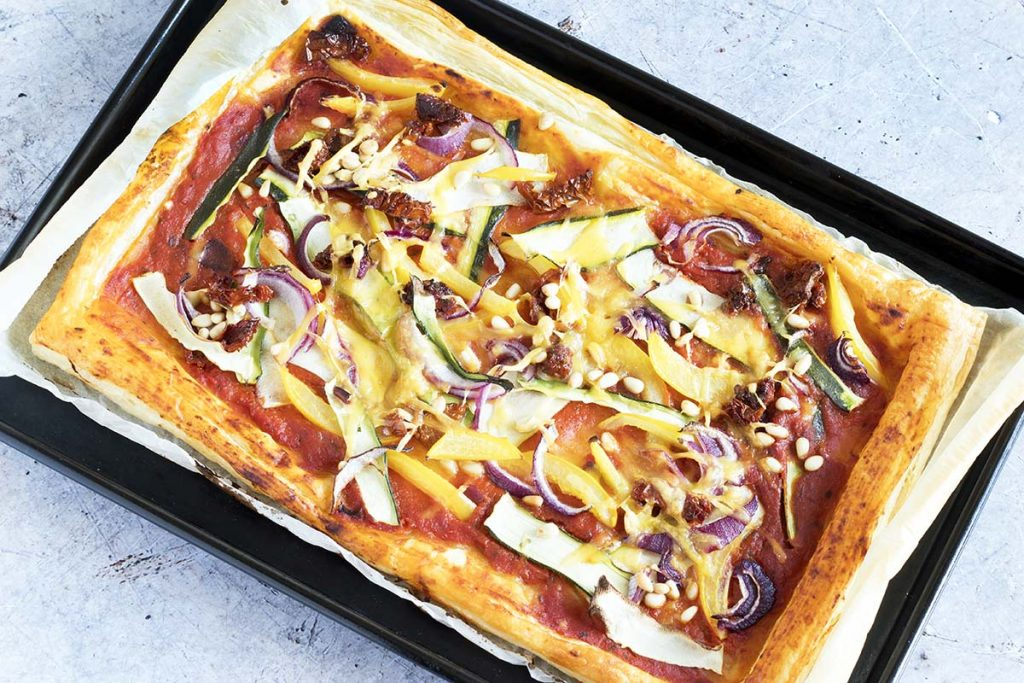 puff pastry tart with vegetables on baking tray