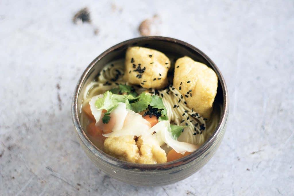 vegan tofu ramen in brown ceramic bowl on grey background