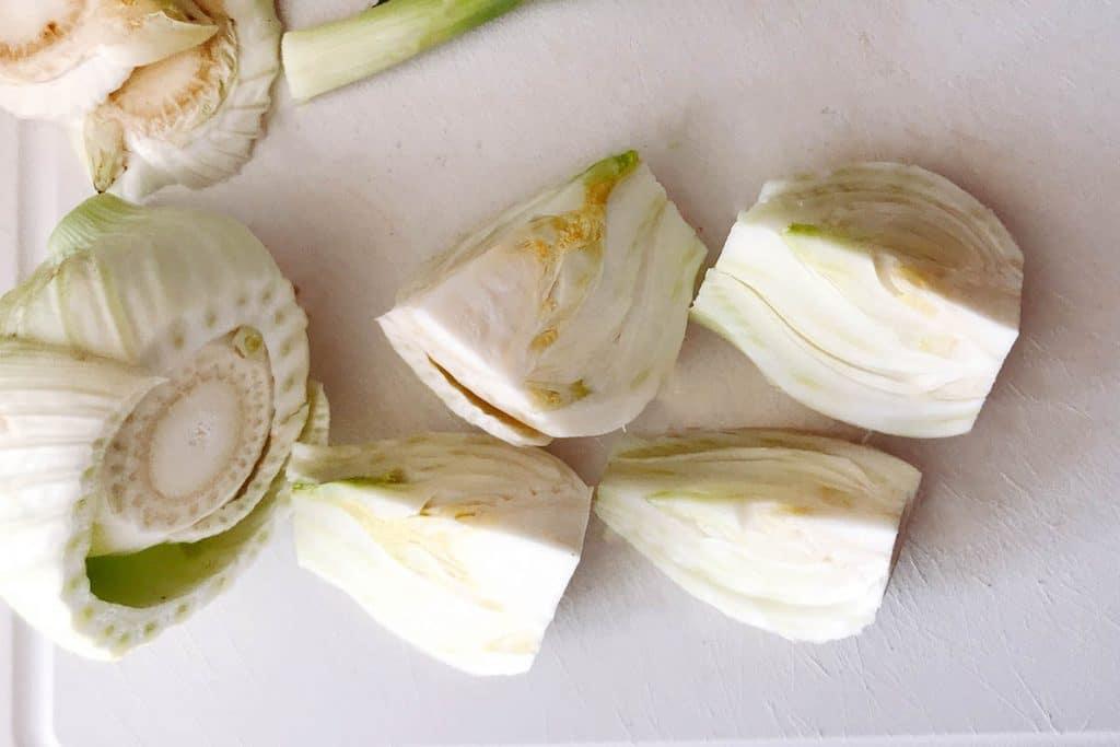 a fennel bulb on chopping board cut into quarters