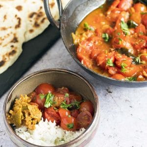 tomato curry with rice, pickle and flatbreads in bowl and dish