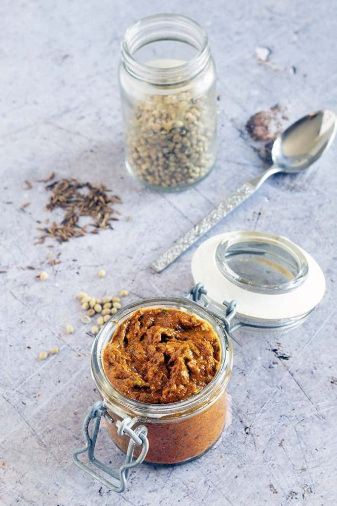 overhead shot of tikka paste in jar with spices in background