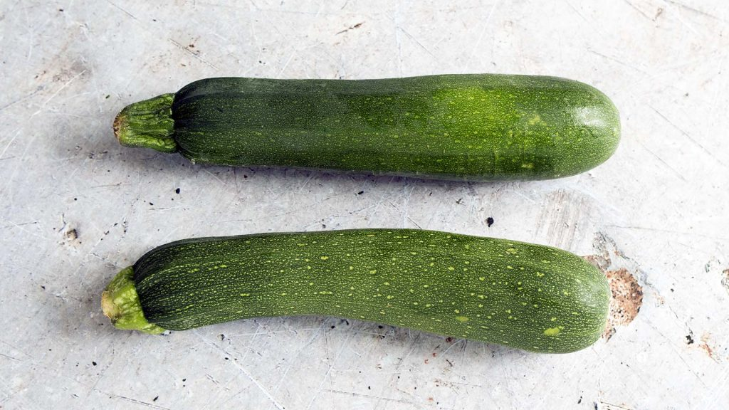 two courgettes on grey background